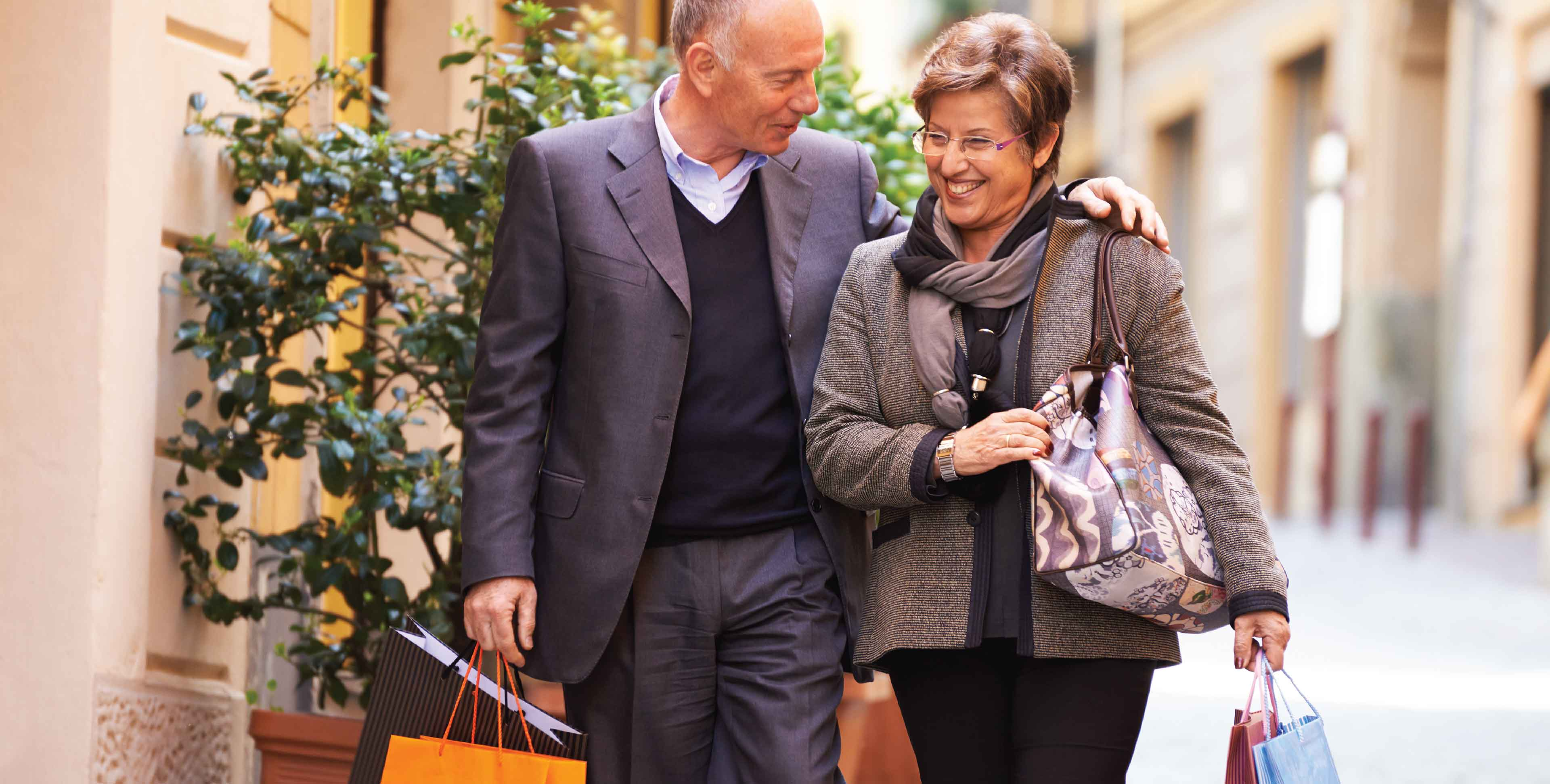 Older couple walking with shopping bags